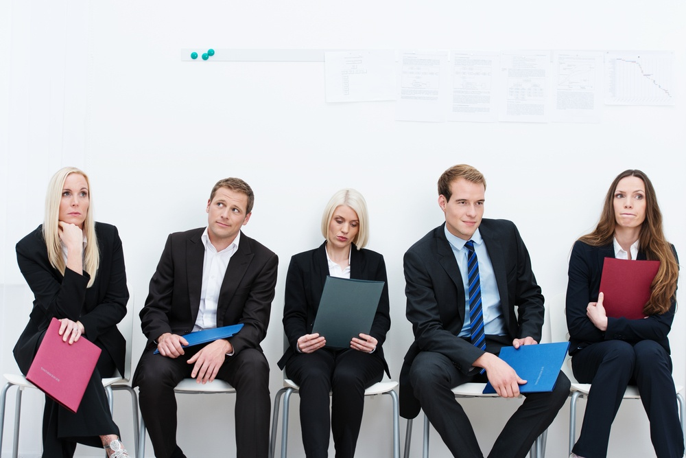 Group of applicants for a vacant post or corporate job sitting in a long line with folders containing their credentials carefully ignoring each other.jpeg