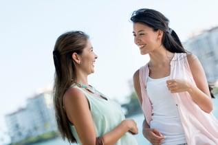 Happy female friends talking and having fun outdoors.jpeg